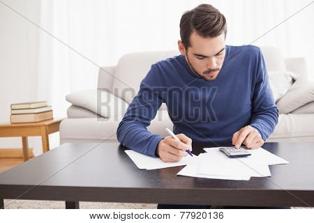 Young man paying his bills at home in the living room