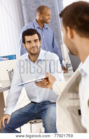 Young businessman sitting on chair reaching out for folder handed by colleague.