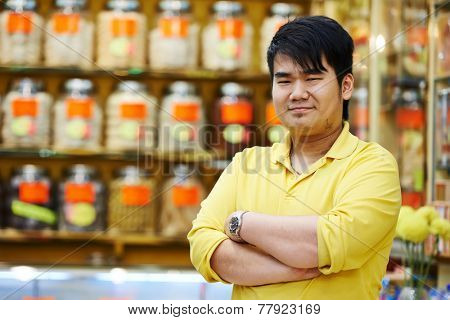 chinese young smiling male assistant seller in the traditional pharmacy shop