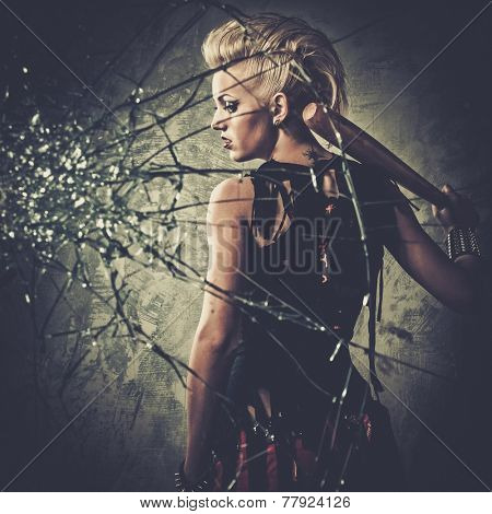Punk girl behind broken glass with a baseball bat
