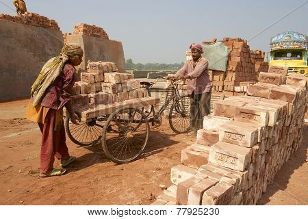 Two workers move bricks at a factory in Dhaka, Bangladesh.