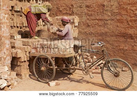 Two workers load bicycle with bricks in Dhaka, Bangladesh.