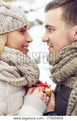 Young amorous man giving small present to his girlfriend and both looking at one another