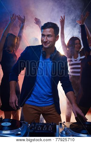 Male deejay leading and enjoying party with happy friends dancing behind