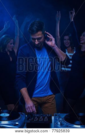 Young stylish deejay at dancing party in night club