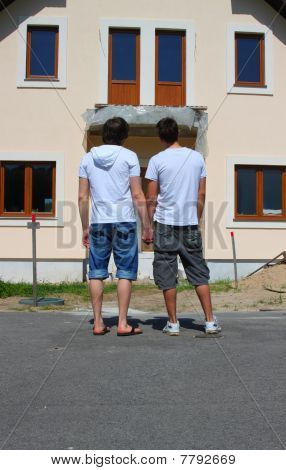 Same-sea couple in front of their new house