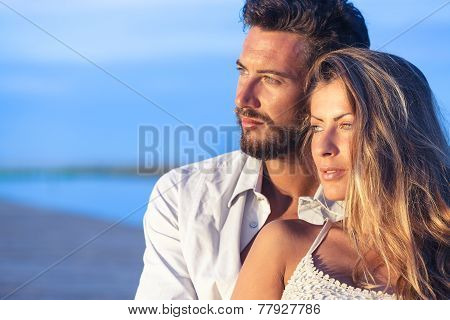Man Embracing His Woman From Behind On Seaside Background Under A Blue Sky