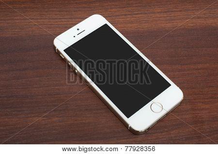 Pavlograd, Ukraine - December 4, 2014: Iphone 5S Gold. Studio Shot On Wooden Background.