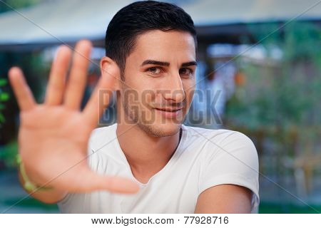 Young Man Rising Hand Making Stop Gesture