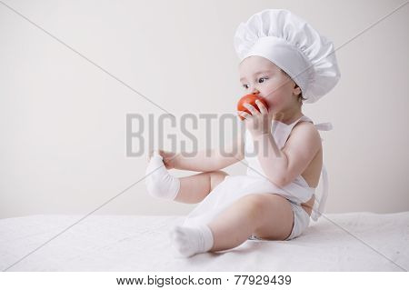 cute little cook eats tomato