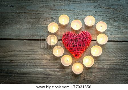 Heart With Burning Candles On The Wooden Background