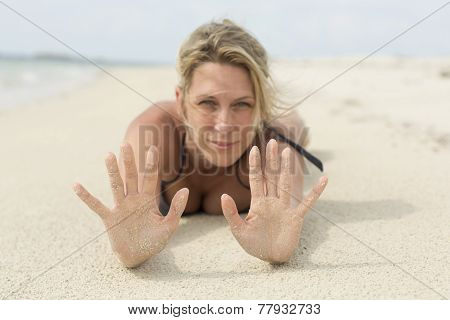 Sandy hands. A beautiful blonde woman lays at the beach.