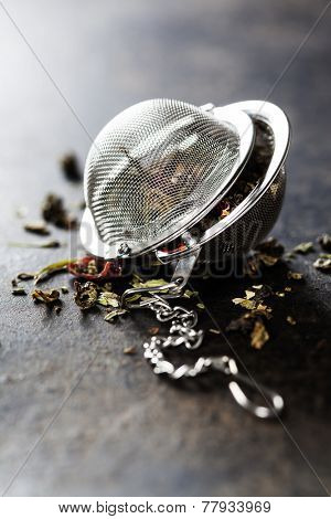 Tea composition with tea strainer on dark background