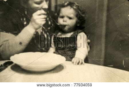 GERMANY, DECEMBER 25, 1938: Mother feeds a little daughter