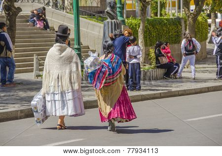 LA PAZ, BOLIVIA, MAY 8, 2014:  Local women in traditional attire walk at Plaza Murillo
