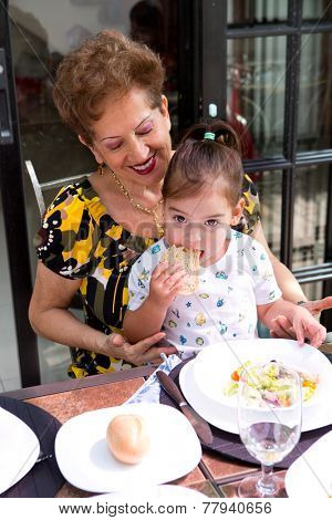 Beautiful little toddler girl sitting on her grandmother's lap while enjoying a slice of bread at mealtime
