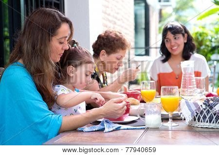 Beautiful hispanic family with a girl toddler having breakfast together on the outdoor dining showing family bonding time.