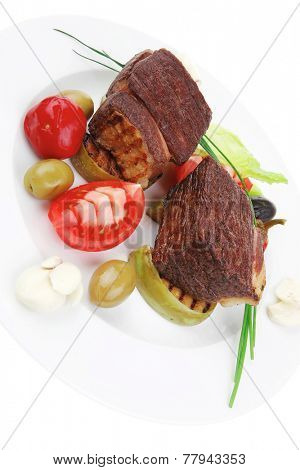 roast meat : beef (pork) steak garnished with baked apples , green and black olives , tomatoes , on white plate isolated over white background