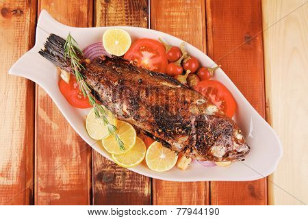 savory: whole fried sunfish over wood with tomatoes lemons and peppers