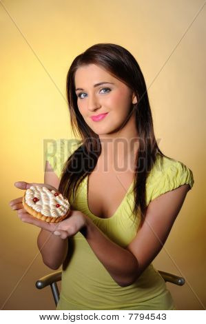Young Beautiful Girl Eating Small Sweet Cake. Yellow Background