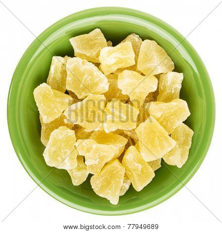 chunks of dried pineapple in an isolated green ceramic bowl