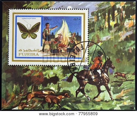 FUJEIRA - CIRCA 1972: A stamp printed in Fujeira shows boy scouts and ornithoptera circa 1972