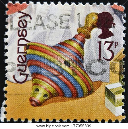 GUERNSEY - CIRCA 1994: A stamp printed in Guernsey dedicated to bygone toys shows a peg-top