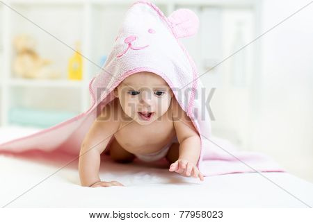 cute baby under the towel after bathing at home