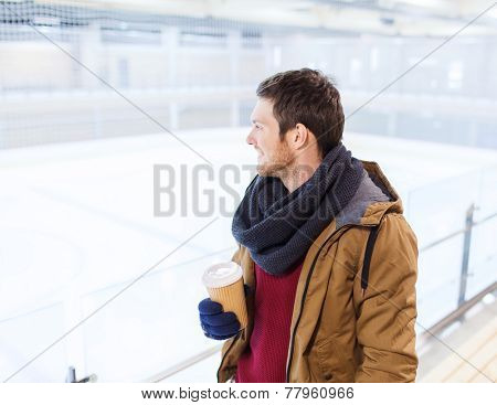 people, hot drinks and leisure concept - happy young man with paper coffee cup on skating rink