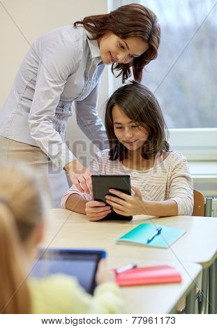 education, elementary school, learning, technology and people concept - little girl with teacher and tablet pc computer in classroom
