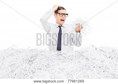 Shocked man looking at a pile of shredded paper isolated on white background