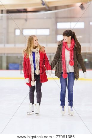 people, women, friendship, sport and leisure concept - two happy girls friends on skating rink