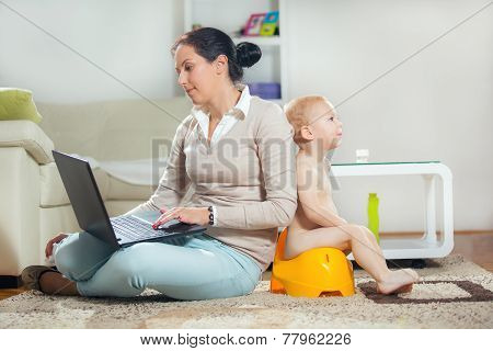 Working mother working at home and not watching his child to the potty