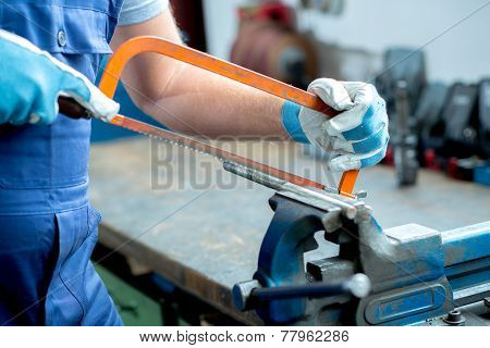 worker with saw on work bench in the factory