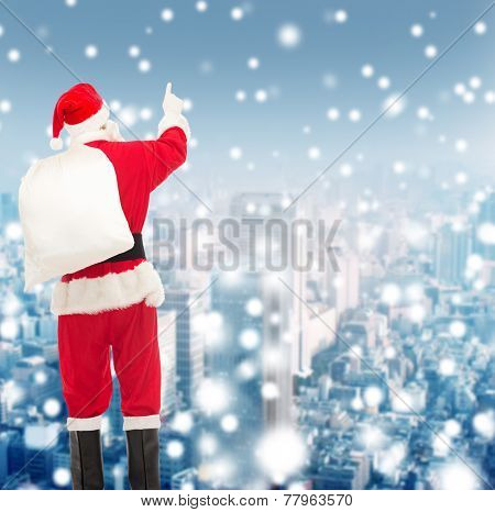 christmas, holidays and people concept - man in costume of santa claus with bag pointing finger from back over yellow lights background over snowy city background