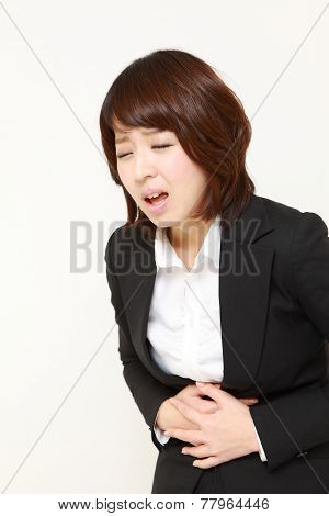 businesswoman suffers from stomachache