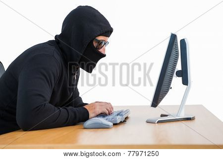 Burglar with sunglasses typing on keyboard on white background