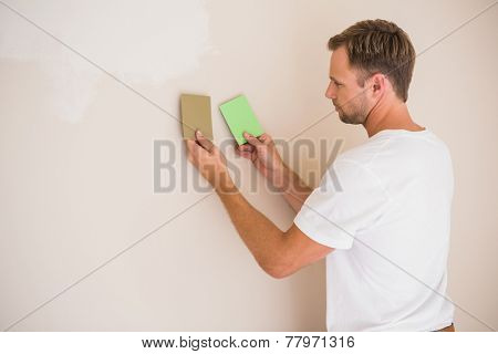Handsome decorator sanding down the wall in a new home