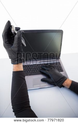 Burglar hacking laptop and mobile phone on white background