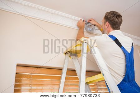 Handyman putting scotch on the ceiling in a new house