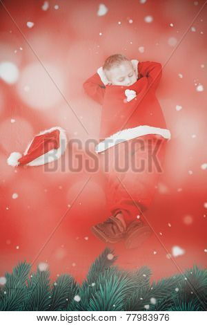 Little boy napping in santa costume against light design over floor boards