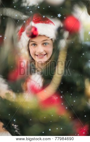 Festive litte girl decorating christmas tree against snow falling