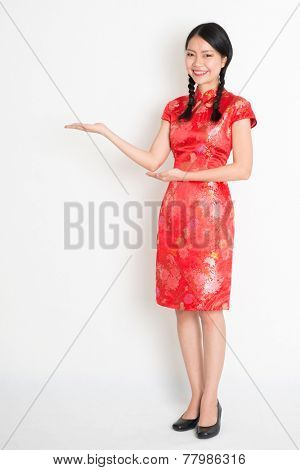 Portrait of full length Asian Chinese girl, hands showing something, in traditional red cheongsam standing on plain background.
