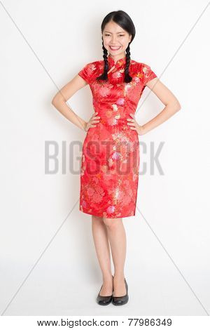 Portrait of full length Asian Chinese girl, in traditional red cheongsam standing on plain background.