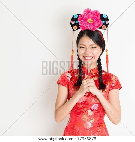 Portrait of Asian Chinese girl with princess hat greeting, in traditional red qipao standing on plain background.