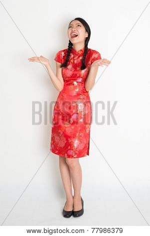 Portrait of full body Asian Chinese girl with excited facial expression, open palms and looking up, in traditional red qipao standing on plain background.
