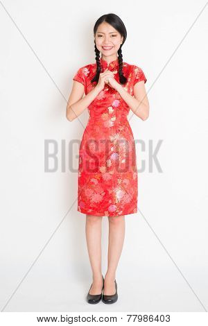 Happy Chinese New Year!! Portrait of Asian Chinese girl blessing, in traditional red qipao standing on plain background.