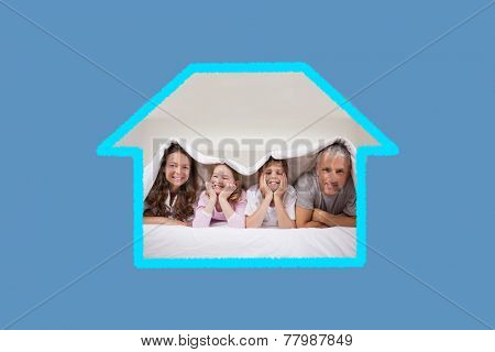 Playful family lying under a duvet against blue background with vignette