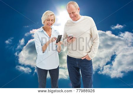 Happy mature couple using their smartphones against blue sky with clouds and sun