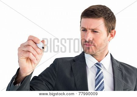 Serious businessman writing with marker on white background